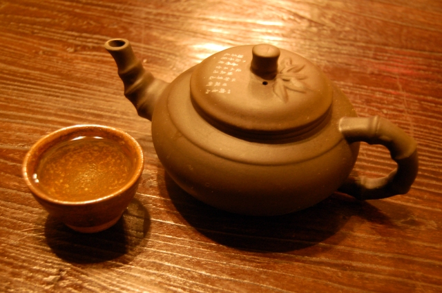 Cup_of_green_tea_and_tea_pot_on_table